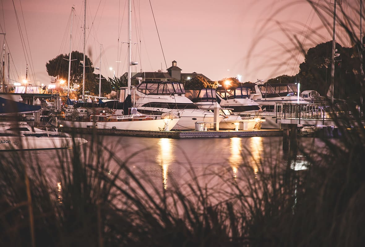 Boats docked at marina at night