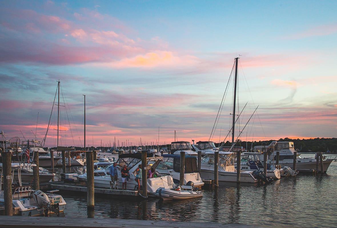 Boats docked at marina at sunset